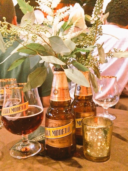 Gorgeous table decorations included simple florals inside Negra Modelo bottles. #branding