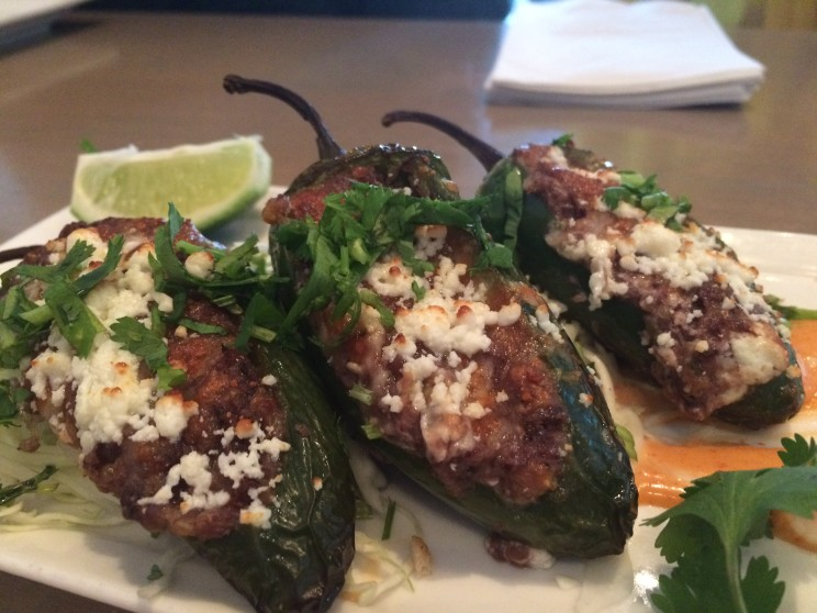 Grilled Jalapeño Poppers stuffed with Stuffed with black beans, quinoa, goat and jack cheese, and sriracha aioli drizzle