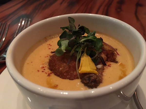 A cup of creamy, spicy corn chowder with a fried mushroom on top